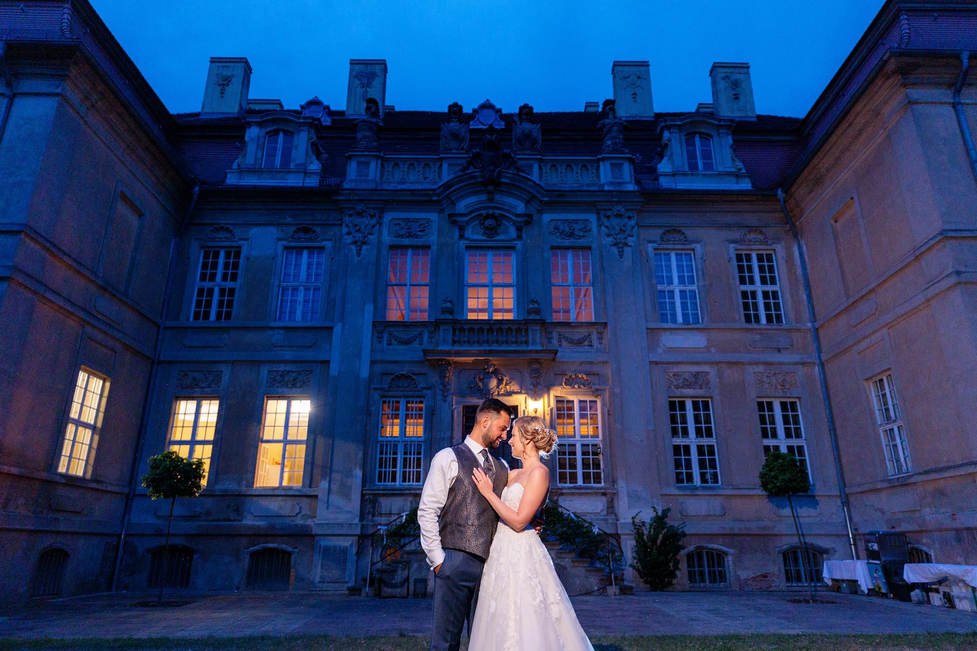 Zur Blauen Stunde entsteht ein Hochzeitsfoto mit dem Brautpaar vor dem Schloss