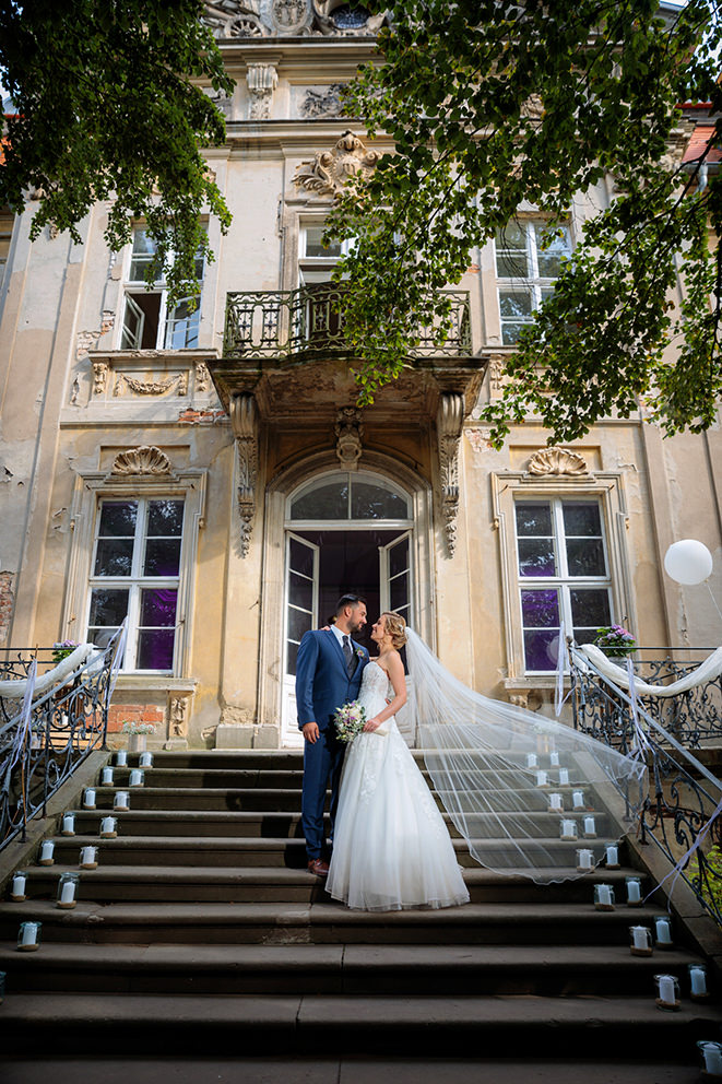 Brautpaar auf Treppe vor dem Schloss Roskow