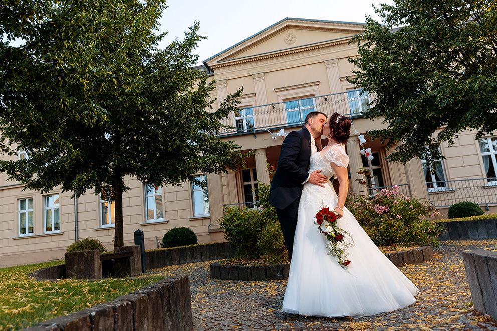 Hochzeitspaar küsst vor Gut Gnewikow am Ruppiner See