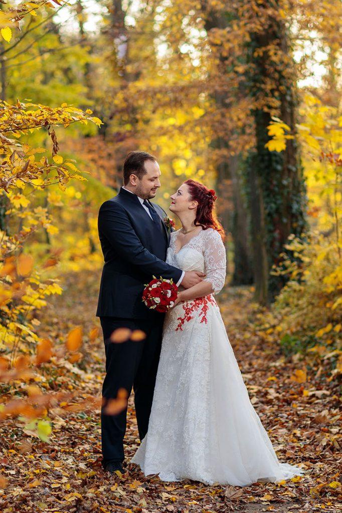Ein Brautpaar im Wald mit Herbstlaub