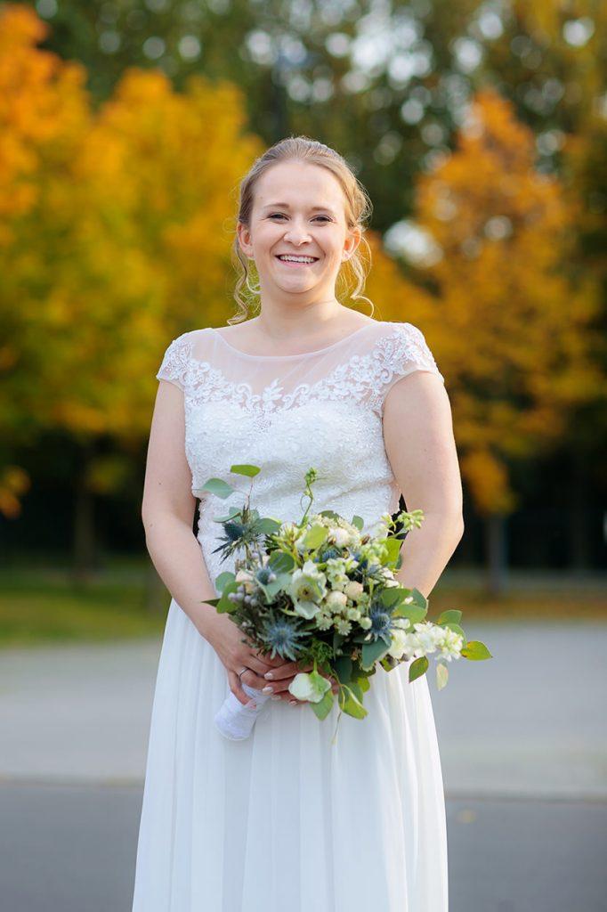 Eine lachende Braut im Herbst