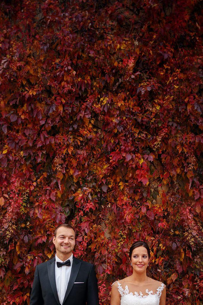 Brautpaar vor einer Blätterwand im Herbst