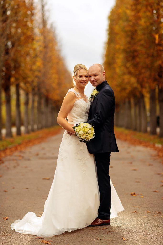 Brautpaar auf einer herbstlichen Baumallee im Park Sanssouci