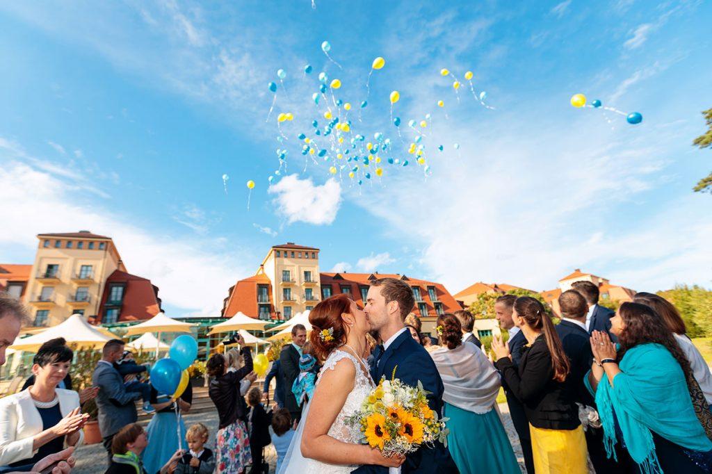Küssendes Brautpaar unter den fliegenden Luftballons