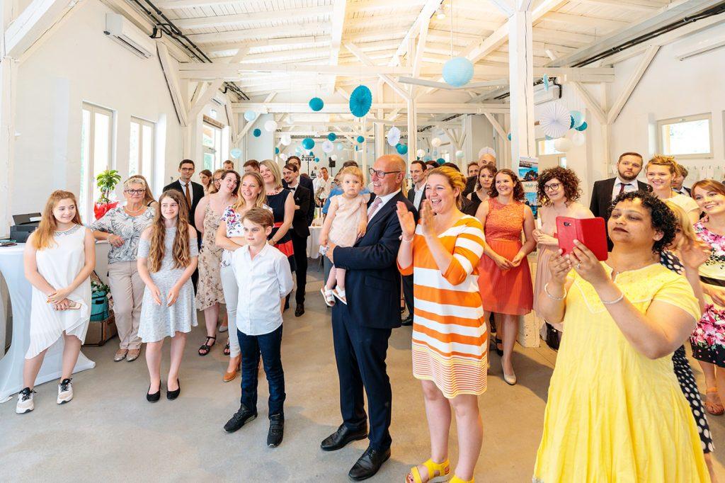 Die Hochzeitsgäste beobachten freudig den Anschnitt der Hochzeitstorte