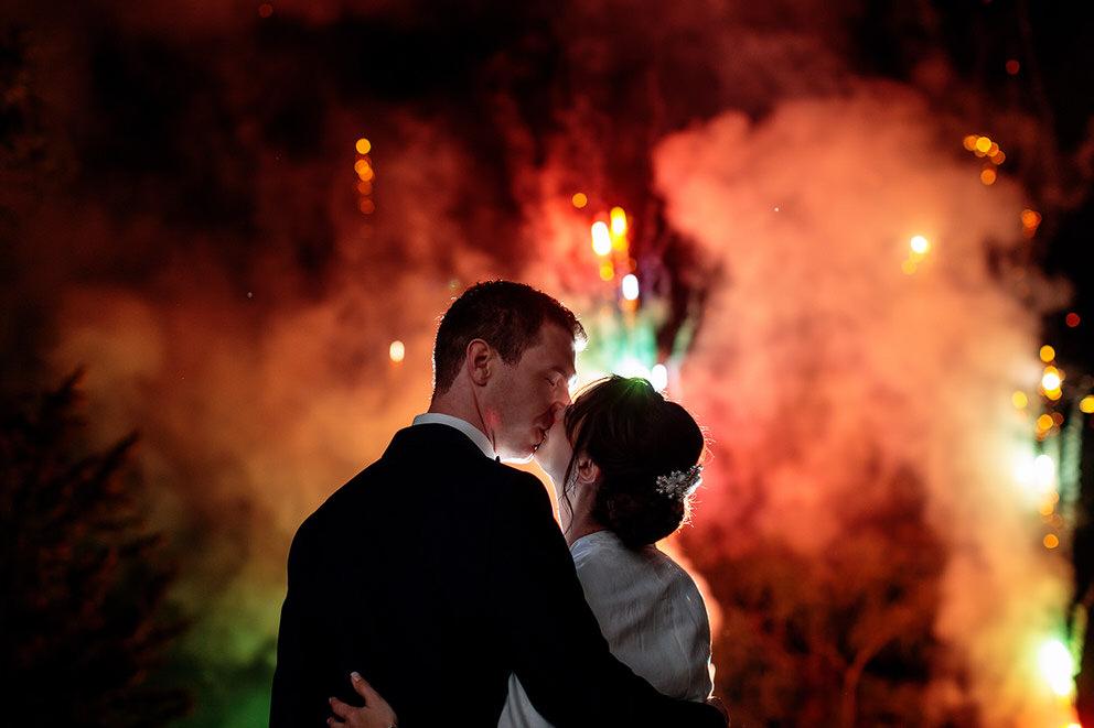 Ein Kuss zwischen dem Brautpaar unter dem Feuerwerk auf dem Landgut Stober