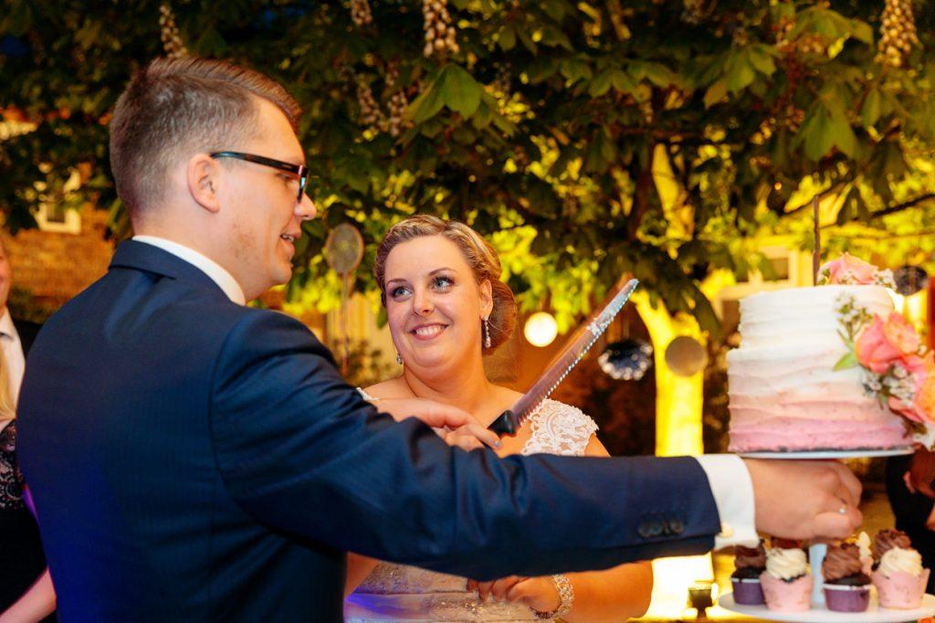 Die Braut blickt ganz verliebt ihren Bräutigam an während sie gemeinsam die Hochzeitstorte anschneiden
