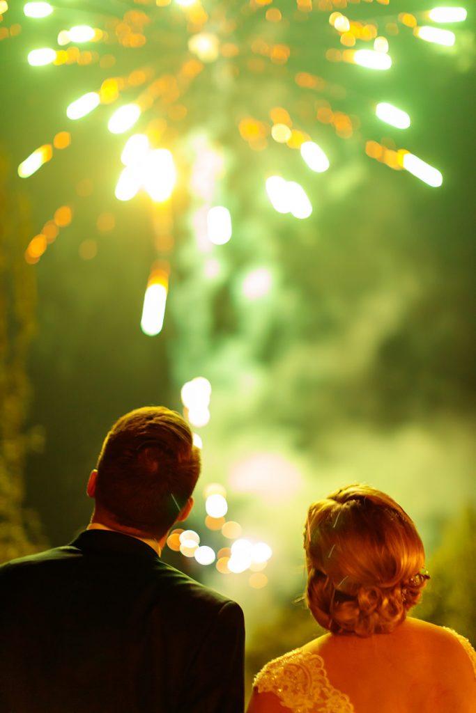 Das Brautpaar beobachtet Seite an Seite das Feuerwerk