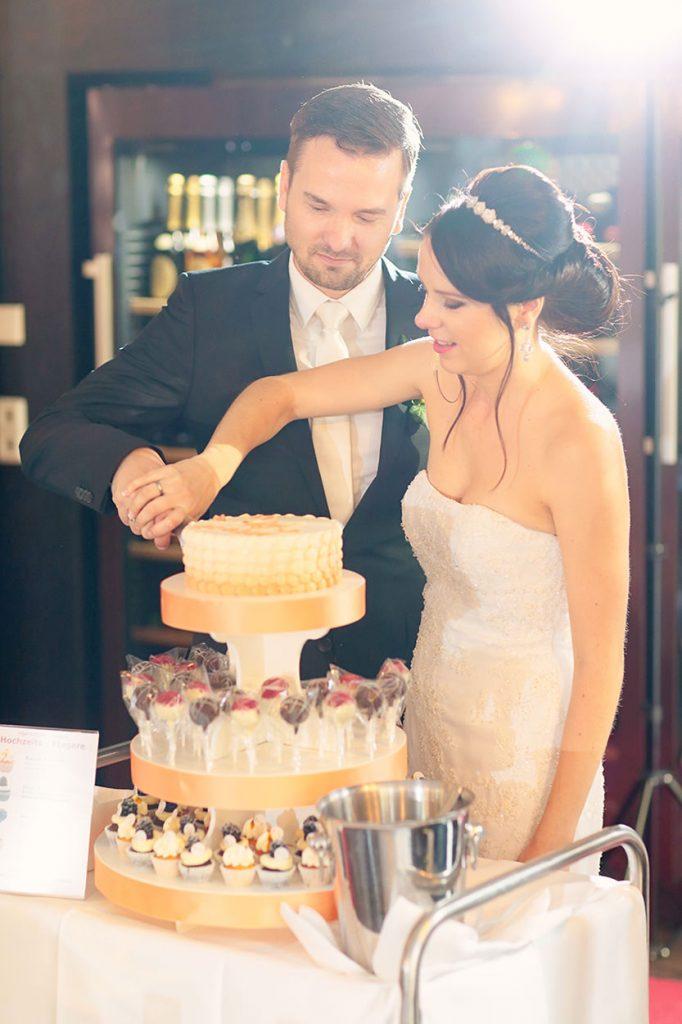 Das Brautpaar schneidet die Hochzeitstorte an