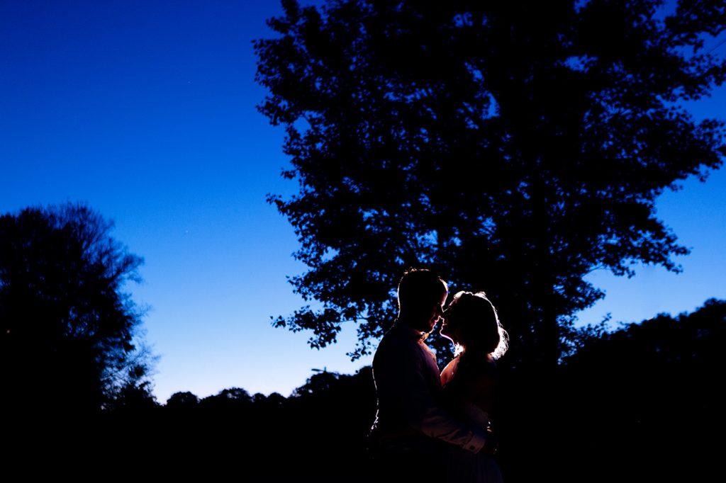 Zart zeichnet sich das Brautpaar vom blauen Abendhimmel ab