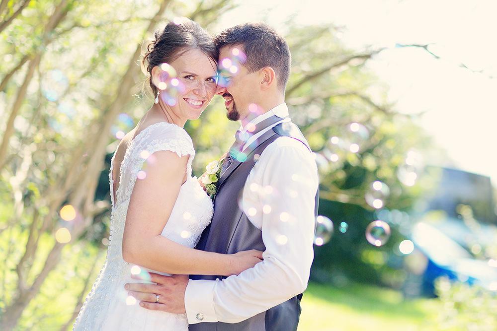 Das Brautpaar umhüllt von Seifenblasen bei den Hochzeitsfotos