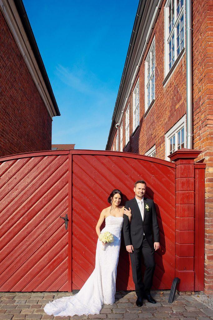 Das Brautpaar vor einem roten Tor