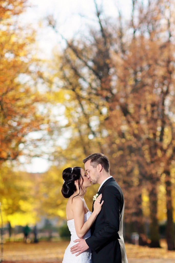 Romantischer Kuss zwischen Braut und Bräutigam im Herbst