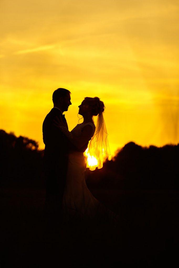 Das Brautpaar als Silhouette im Sonnenuntergang