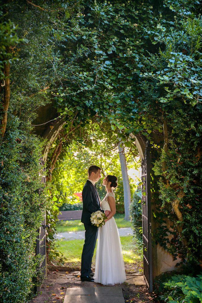 Brautpaar unter einem von Pflanzen bewachsenen Tor