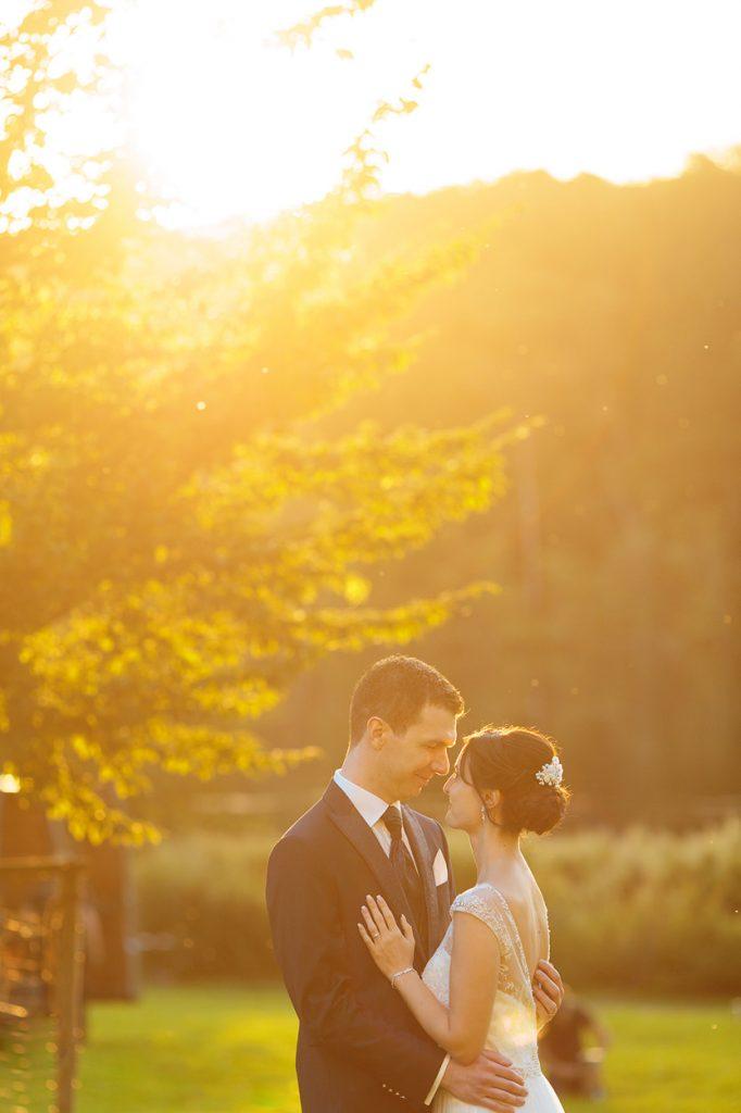Romantische Moment zwischen dem Brautpaar während der Fotos im Sonnenuntergang