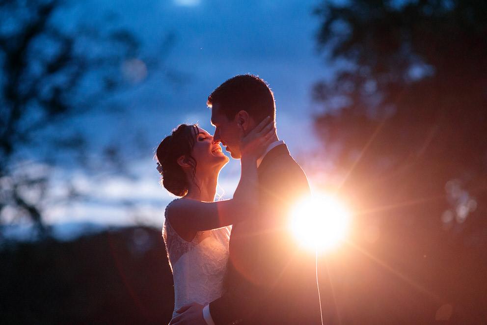 Liebevolle küsst die Braut ihren Bräutigam auf dem Landgut Stober