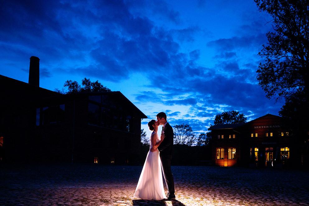 Ein küssendes Brautpaar zur Blauen Stunde auf dem Landgut Stober