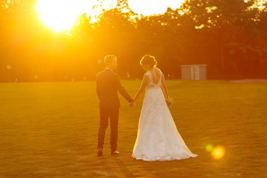 Das Brautpaar spaziert dem Sonnenuntergang entgegen