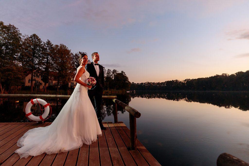Das Brautpaar auf dem Steg zum Sonnenuntergang am Plessower See