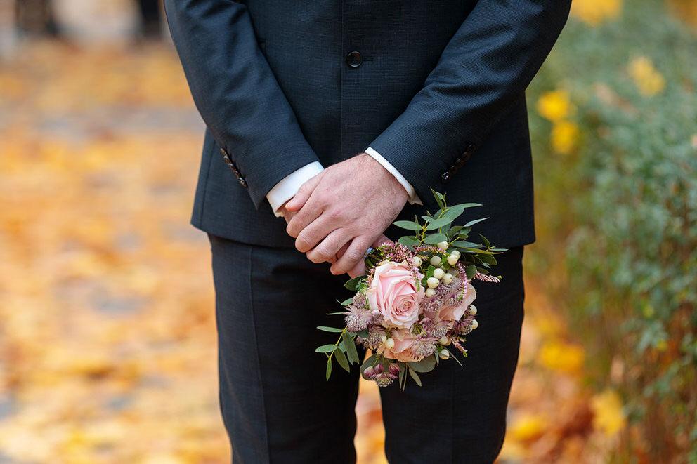 Der Bräutigam hält den Brautstrauß