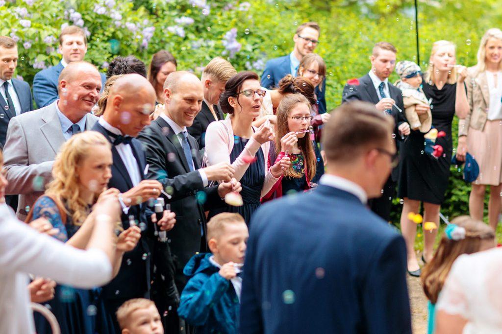 Und die Hochzeitsgäste bejubeln das Brautpaar nach der Trauung