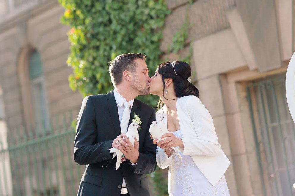 Brautpaar lässt weiße Tauben fliegen