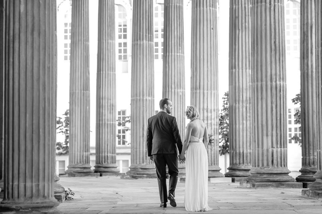 Das Brautpaar schlendert durch die Säulengänge am Neuen Palais in Potsdam