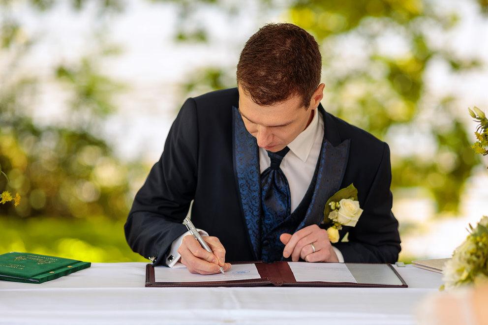 Der Bräutigam unterschreibt die Dokumente