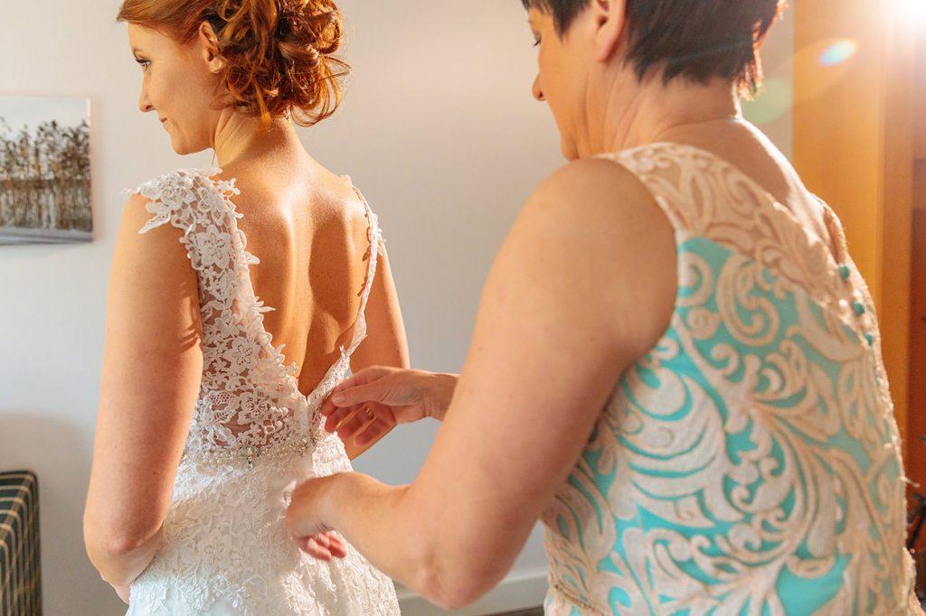 Die Brautmutter macht der Braut das Kleid zu