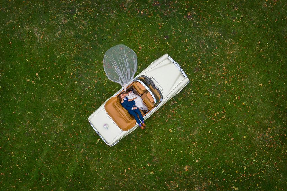 Drohnenfoto mit Brautpaar im Mercedes Cabrio auf Schloss Lübbenau