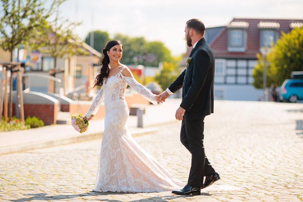 Braut schlendert mit ihrem Mann am Hafen entlang