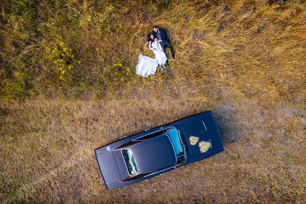 Drohnenbild mit Hochzeitsauto und Paar im Gras