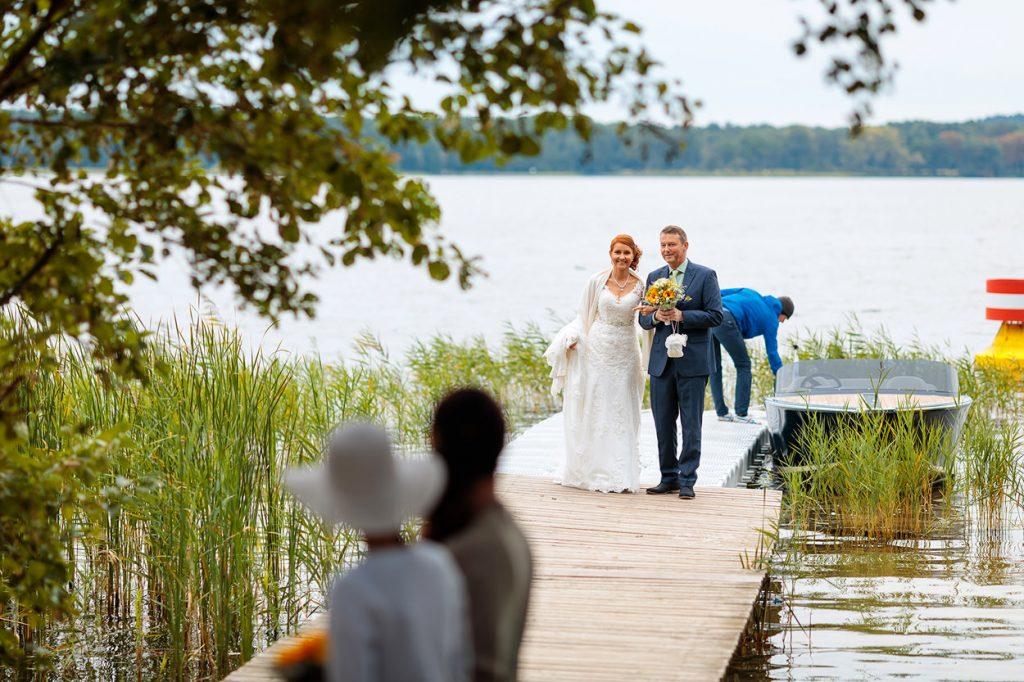 Der Brautvater geleitet seine Tochter den Steg entlang