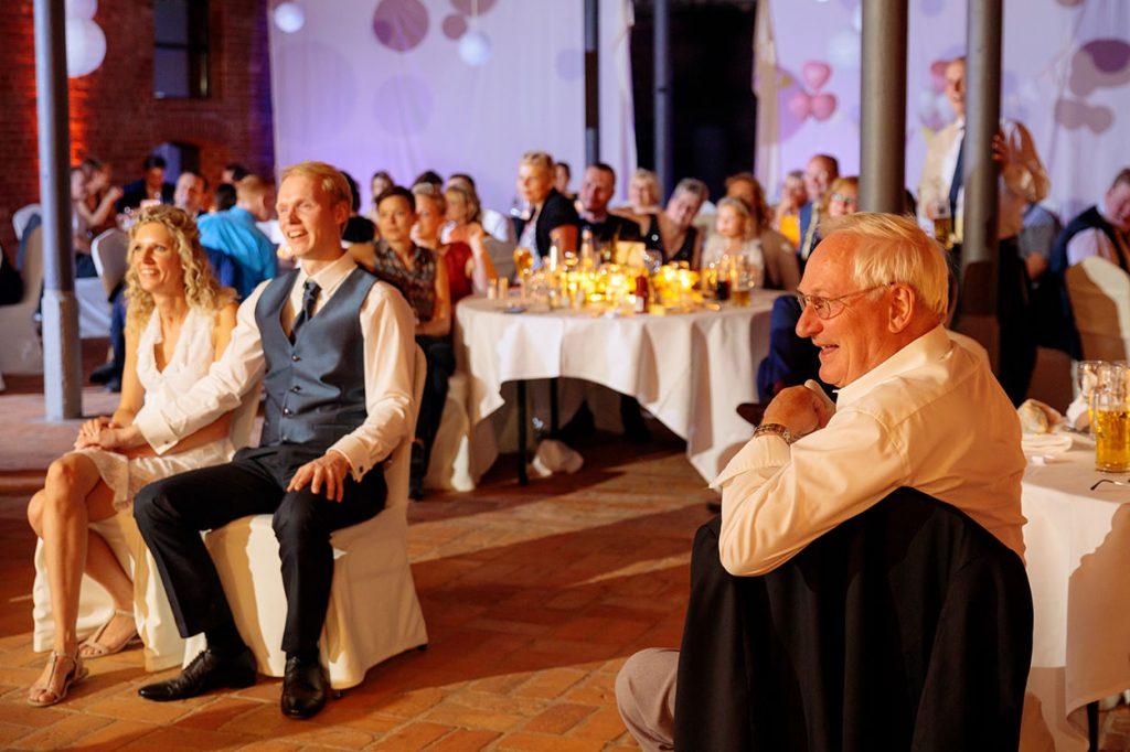Das Brautpaar schaut gespannt eine Hochzeitsspiel zu während der Hochzeitsfeier im Landgut Stober