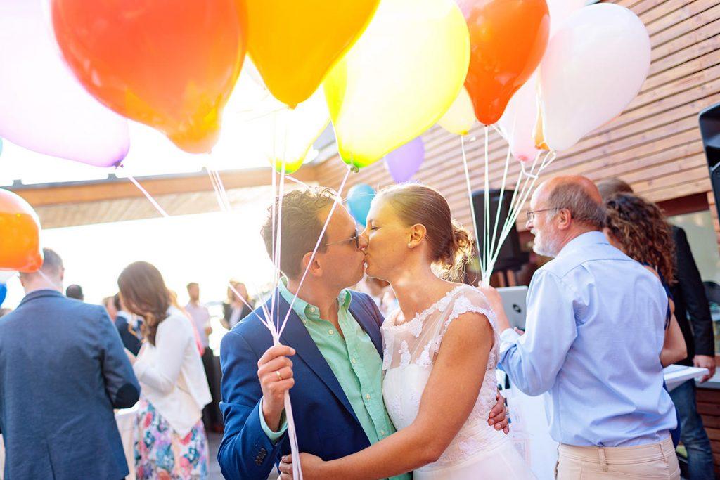 Das Brautpaar mit Luftballons bei der Hochzeitsfeier im Sommer