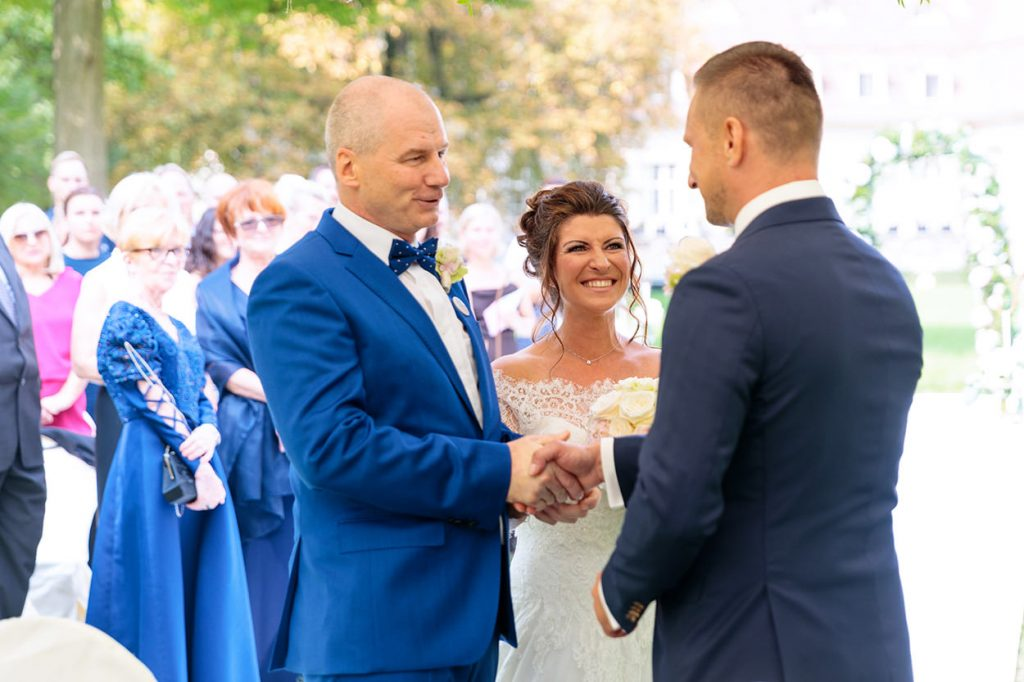 Der Brautvater übergibt die Hand der Braut an den Bräutigam