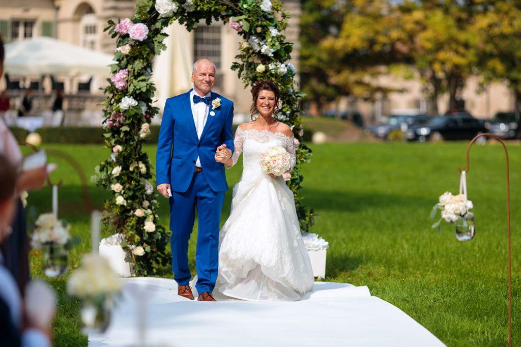 Der Brautvater geleitet seine Tochter zur freien Trauung im Park von Schloss Kartzow