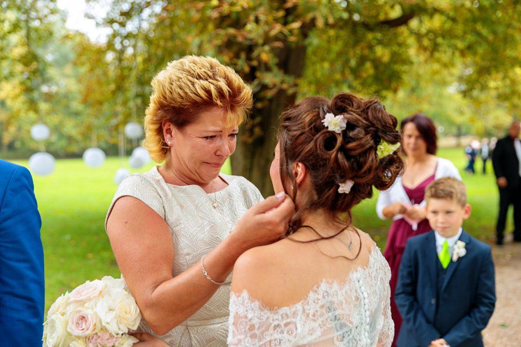 Die Brautmutter beglückwünscht ihre Tochter unter Tränen nach der freien Trauung im Park von Schloss Kartzow Potsdam
