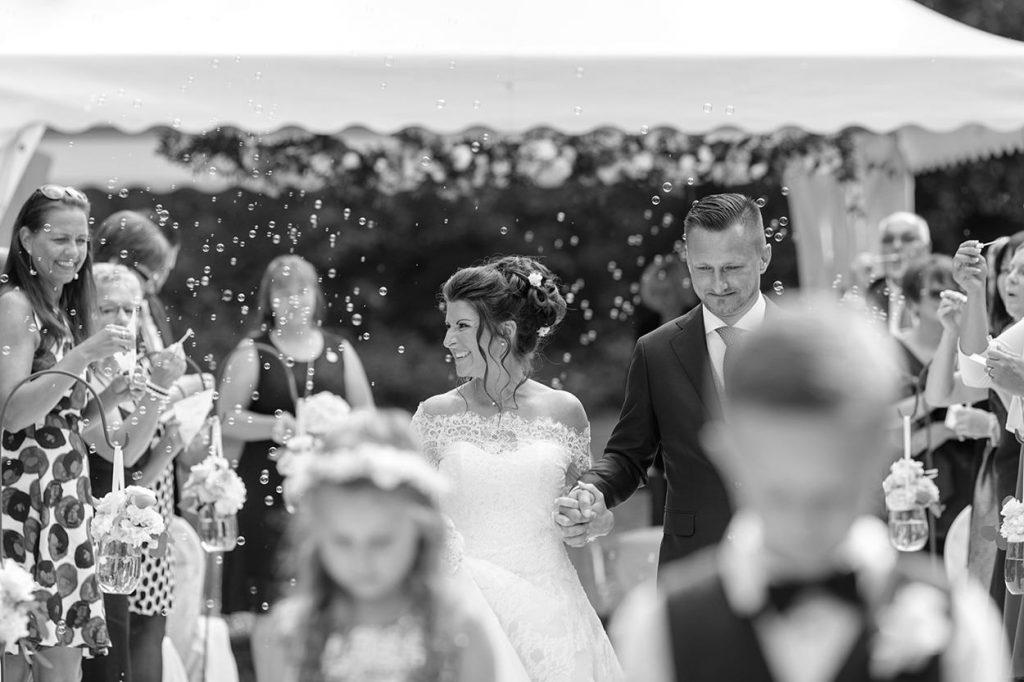 Das Brautpaar in einem Seifenblasenmeer nach der freien Trauung im Park von Schloss Kartzow