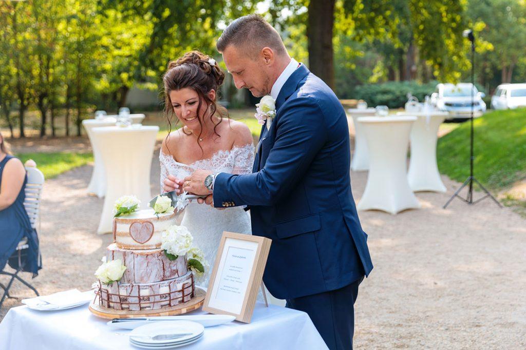 Anschnitt der Hochzeitstorte, die als besonderes Geschenk von der Trauzeugin gebacken wurde