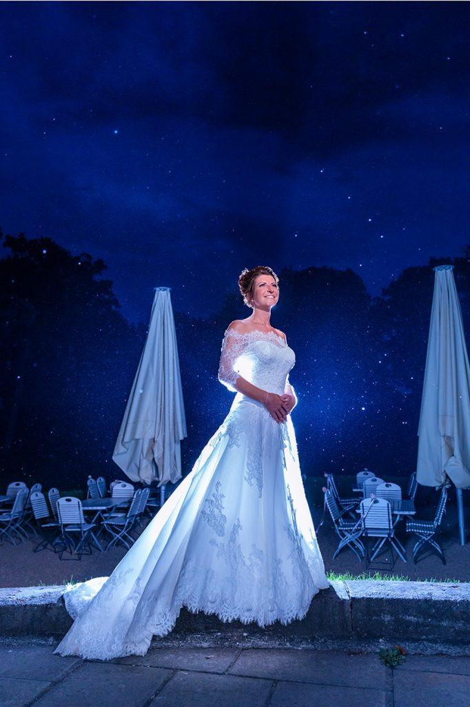 Fotos von der Braut zur Blauen Stunde machen sich besonders gut durch das weiße Hochzeitskleid