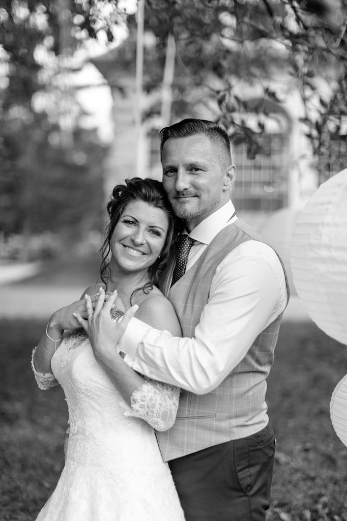Innig umarmt der Bräutigam seine Braut während der Hochzeitsfotos zum Sonnenuntergang im Park von Schloss Kartzow