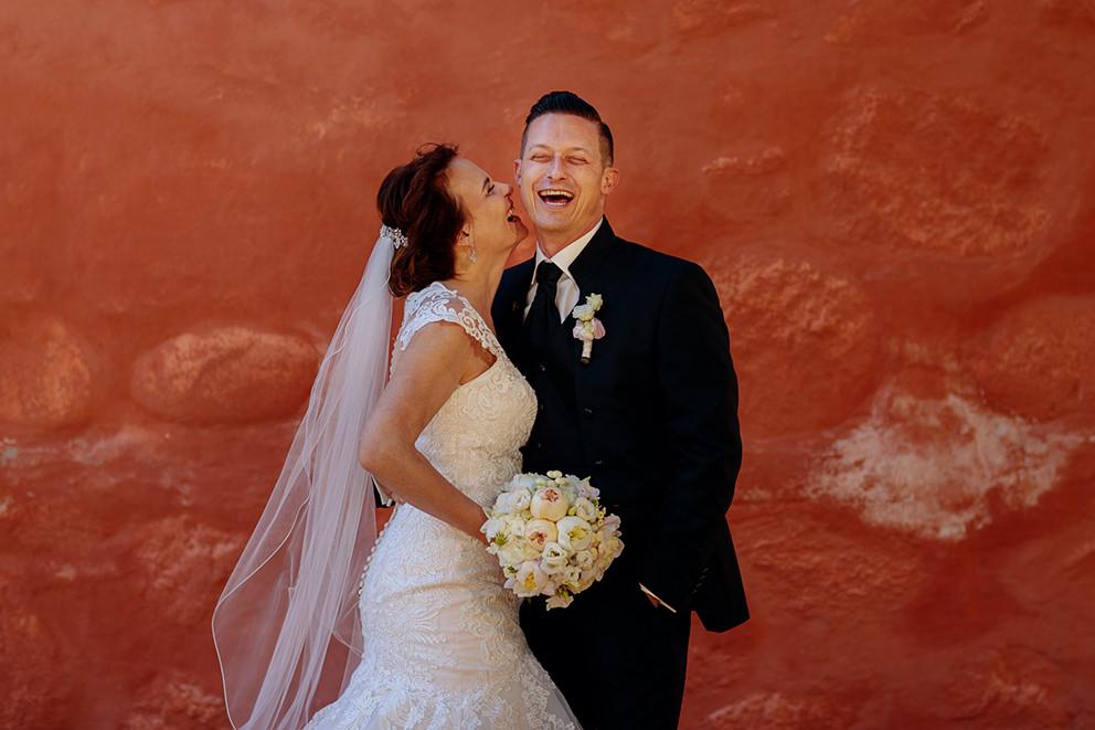 Fröhlicher Bräutigam mit Braut vor der Kirche