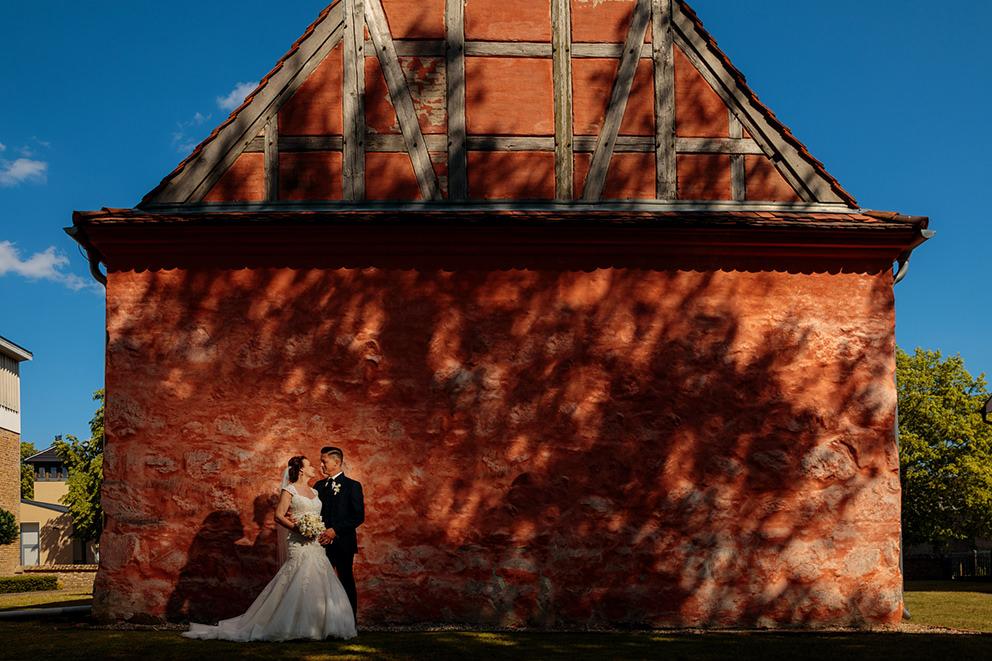 Vor einer roten Kirche bei Werder steht ein von der Sonne angeleuchtetes Paar