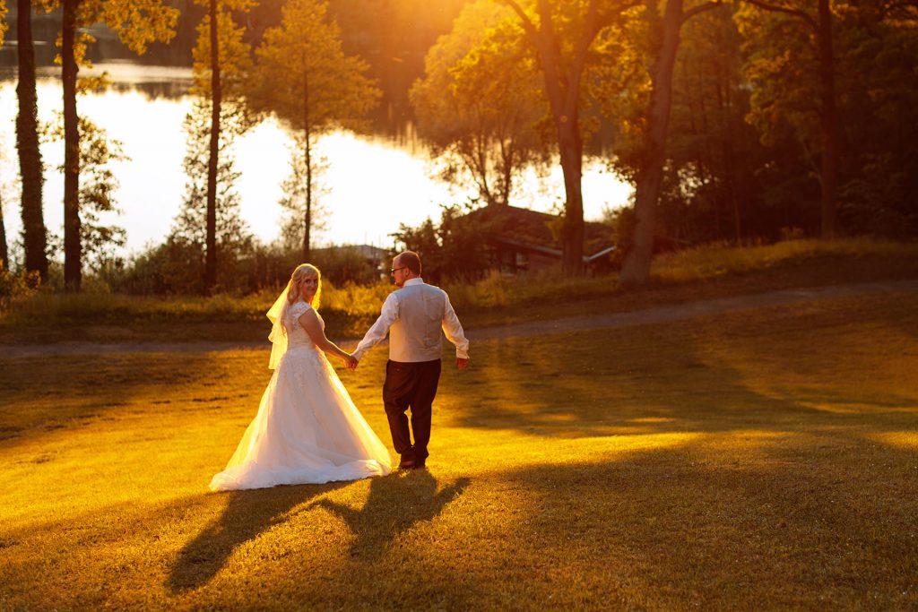 Sommerhochzeit Brautpaar schlendert in den Sonnenuntergang von Schloss & Gut Liebenberg in Brandenburg