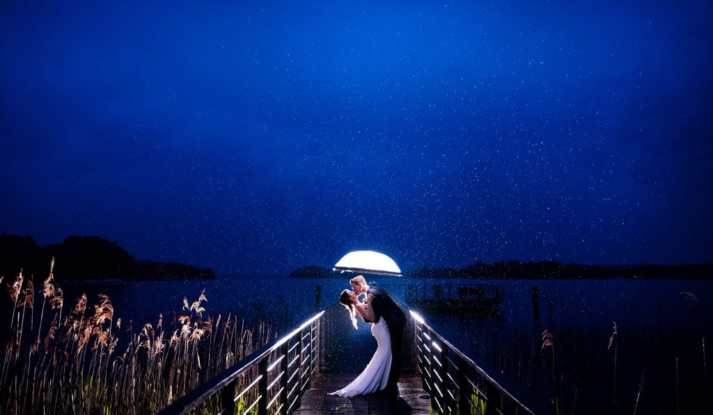 wedding photo of couple in rain at lake in blue hour