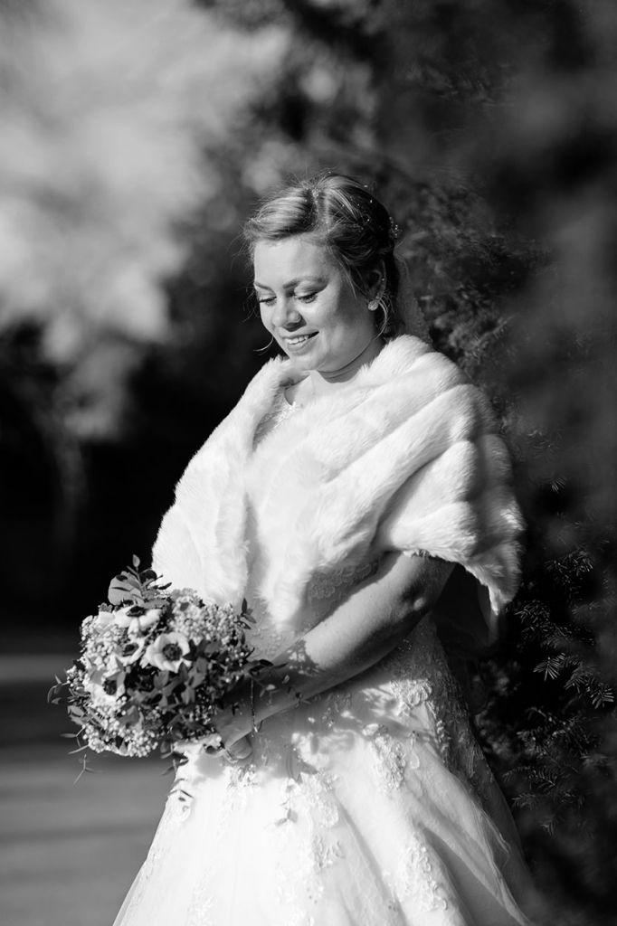Braut mit Fellstola im Park