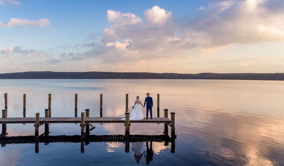 Brautpaar Händchen haltend am Steg in Potsdam bei Sonnenuntergang