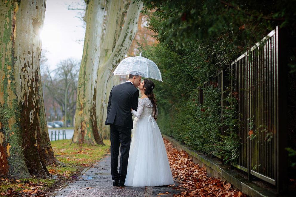 Brautpaar spaziert unter Schirm im Regen